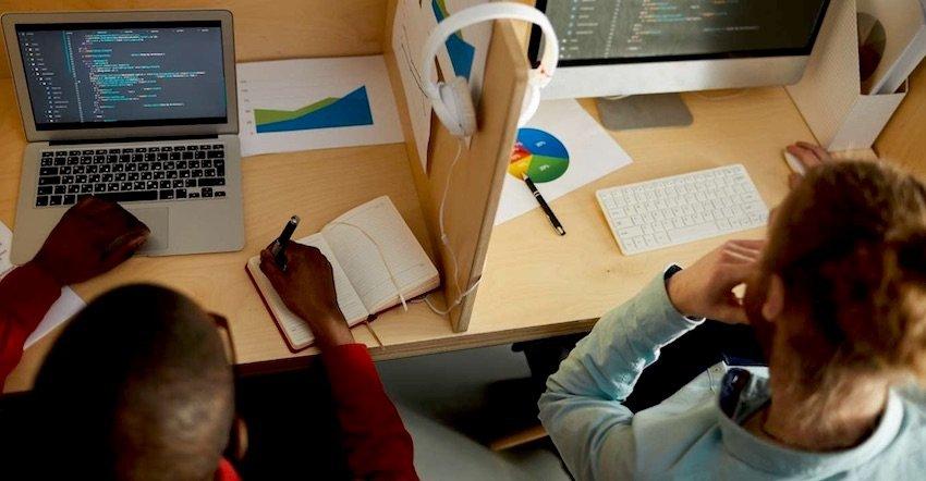 Dois desenvolvedores trabalham em seus workstations